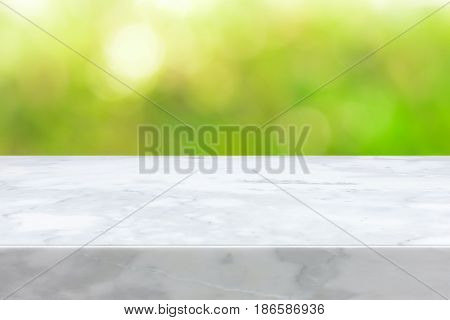 White marble stone countertop on green bokeh abstract background - can be used for display or montage your products