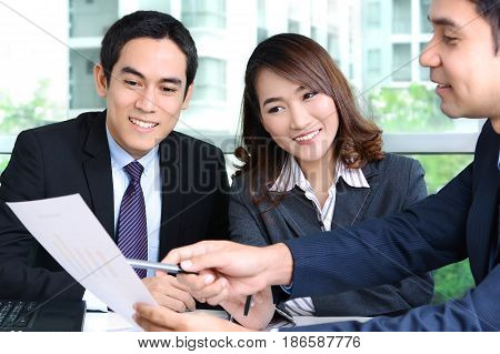Asian business people discussing document in a meeting