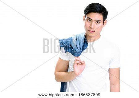 Portrait of young handsome Asian man in white t-shirt holding jean shirt - isolated on white background