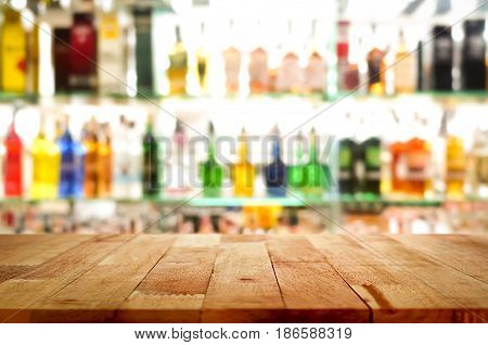 Wood bar top on blur colorful alcohol drink bottle background - can be used for display or montage your products