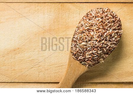 Close up brown rice in wooden spoon. top view