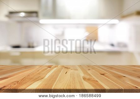 Natural pattern wood table top (or kitchen island) on blur kitchen interior background - can be used for display or montage your products