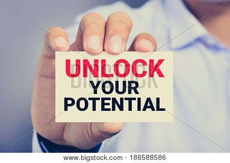 Hand showing card with message UNLOCK YOUR POTENTIAL