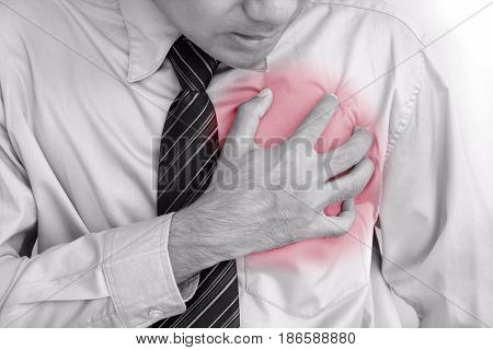Businessman having heart attack - monochrome effect with red spot on pain area