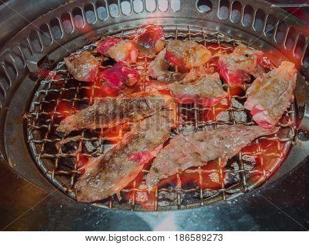Sliced beef on hot charcoal grill yakiniku restaurant.