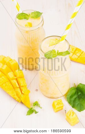 Freshly blended yellow mango fruit smoothie in glass jars with straw mint leaves mango slices close up. Soft white wooden board background.