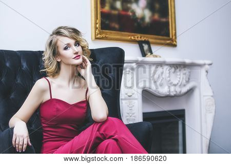 Beautiful woman blonde model in a red jumpsuit a fashionable and elegant luxury interior