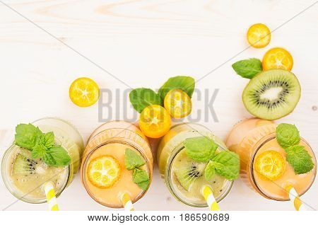 Orange kumquat and green kiwi fruit smoothie in glass jars with straw mint leaf cut ripe berry top view. White wooden board background copy space.