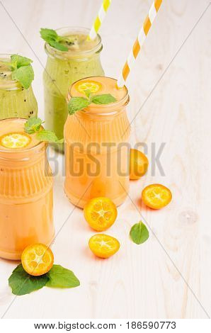 Orange kumquat and green kiwi fruit smoothie in glass jars with straw mint leaf cut ripe berry close up. White wooden board background vertical.