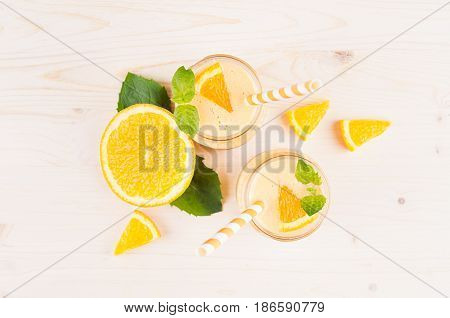 Freshly blended orange citrus smoothie in glass jars with straw mint leaf cut orange top view. White wooden board background copy space.