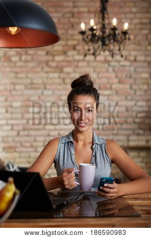 Happy young woman holding tea mug and mobilephone, sitting at desk.