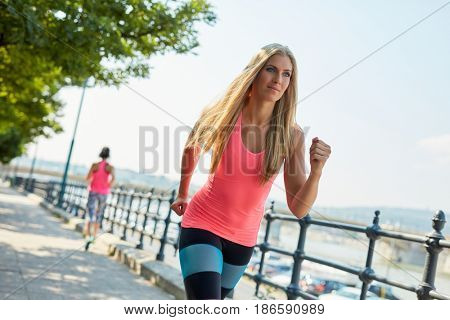 Pretty young blonde woman training outdoors.