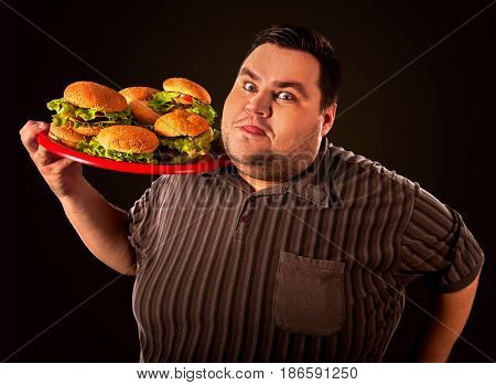 Fat man eating fast food hamberger and carries treat for friends on tray. Breakfast for overweight person. Junk meal leads to obesity. Person regularly overeats concept on black background. Fatso with
