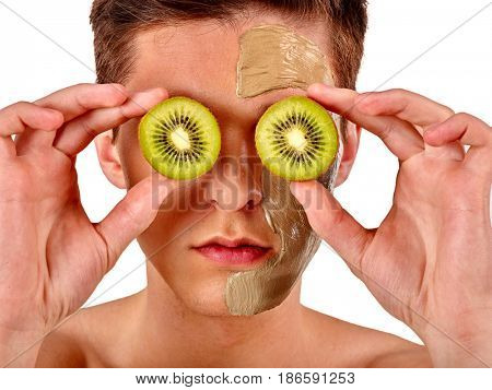 Facial mask from fresh fruits and clay for man concept. Face with treatment mud applied. Male holding kiwi half for skin care procedure in salon.