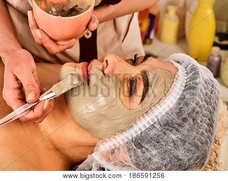 Collagen face mask. Facial skin treatment. Face of woman of elderly woman 50-60 years old receiving cosmetic procedure in beauty salon close up . Professional cosmetologist.
