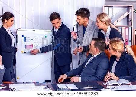 Business people office life of team people working with papers sitting table . Cabinets with folders and jalousie background. Schemas and diagrams on presentation and demonstration .