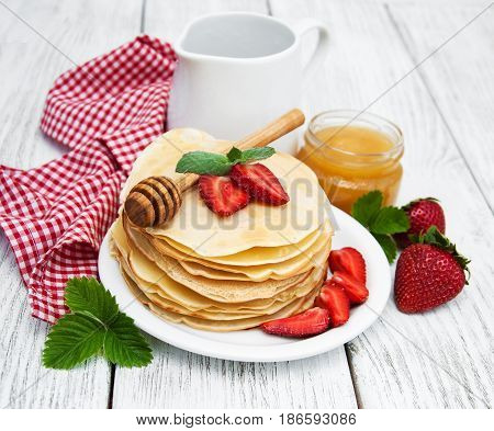pancakes with strawberries on a wooden table