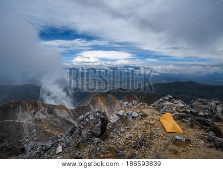 Camping tent on the top of the mountain. Summit of Sibayak Volcano. Scenic panoramic view of volcanic caldera. Berastagi North Sumatra Indonesia.