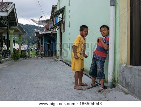 BERASTAGI INDONESIA 15 MAY 2017 : Two indonesian children near the wall on the street at countryside area of Berastagi city Northern Sumatra.