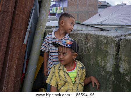 BERASTAGI INDONESIA 15 MAY 2017 : Two indonesian boys near the wall on the street at countryside area of Berastagi city Northern Sumatra.