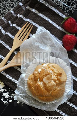 Above of Choux cream with spoon and fork on stripe background