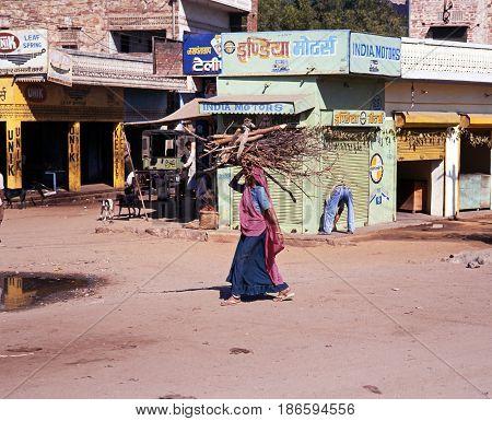 JAIPURA, INDIA - NOVEMBER 22, 1993 - Indian woman walking along a village street carrying firewood on her head Jaipura Rajasthan India, November 23, 1993.