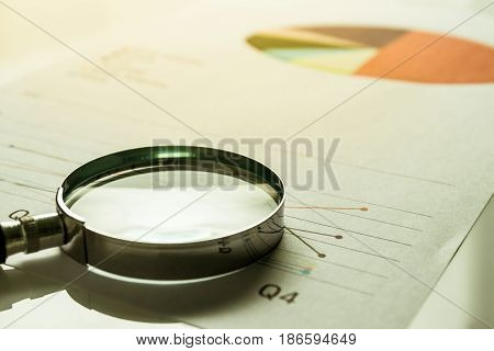 Business summary reports and a magnifying glass with on table office. Concept of Data Analysis Investment Planning Business Analytics.
