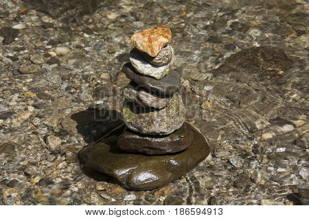 Stones balanced on top of each other in the water collected from a waterfall in the Himalayas, India