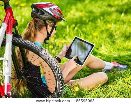 Woman traveling bicycle in summer park. Bicyclist girl watch on tablet computer. Girl counts pulse after sport training and is looking for way to navigator. . Girl is going to do selfie.