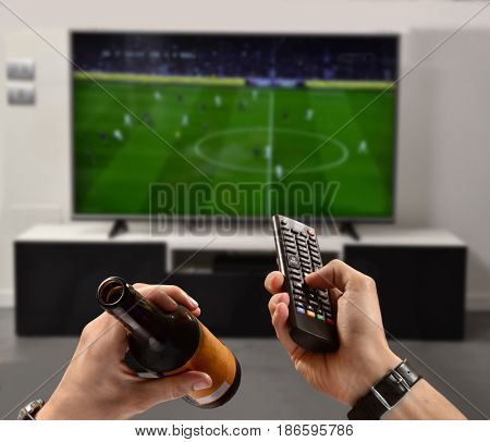 Watching the football game drinking beer holding television control.