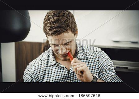 Handsome man eating carrot.
