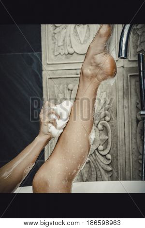 Bathing woman cleaning her leg with sponge.