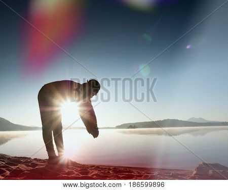 Deep Breathing Runner Silhouette Bended  With Hands On Knees. Side View To Man Stretching Muscles