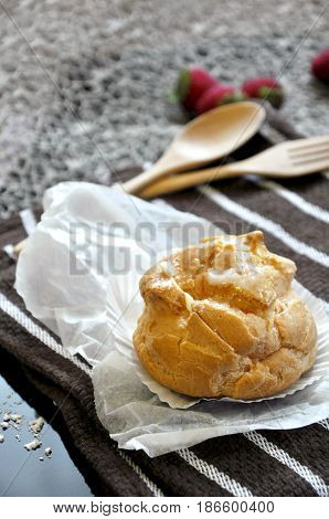 Close up Choux cream with wooden fork and spoon on background