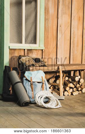 Different Trekking Equipment On Bench Near Wooden House Waiting For Traveler