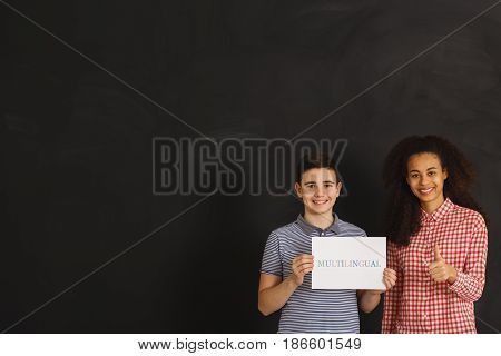 Boy And Woman Holding Card With Multilingual Inscription