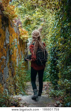 Young woman with blonde dreadlocks with photocamera observe jungle. Adventure and travel.