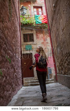 Girl with blonde dreadlocks with camera explores old portugese town. Adventure and travel.