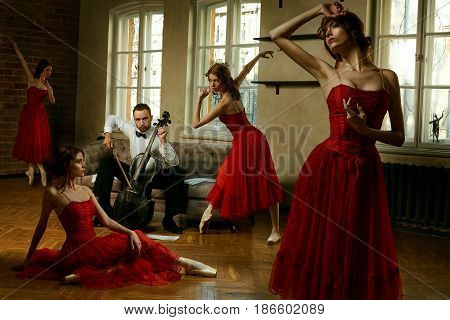 Caucasian handsome male playing on antique black cello and four ballerina in red dress dancing around him
