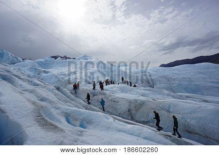 A line of people walk along the the ridges of Perito Moreno Glacier in Patagonia, Argentina