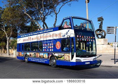 FLORIANA, MALTA - MARCH 30, 2017 - Passengers aboard a bus open topped tour bus with the Independence Monument to the rear Floriana Malta Europe, March 30, 2017.