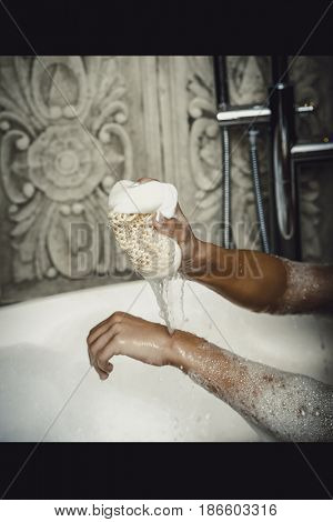 Bathing woman cleaning herself with sponge.