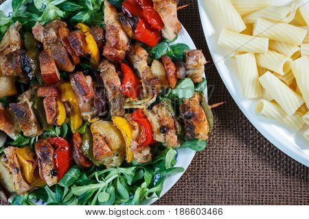 Grilled meat skewers - grilled pork kebab with red and yellow pepper on a plate with vegetables