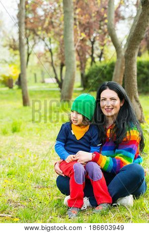 Happy family in colorful clothes sitting in grass in park