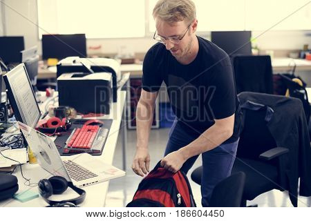Man Grabbing Backpack Leaving After Work Hour
