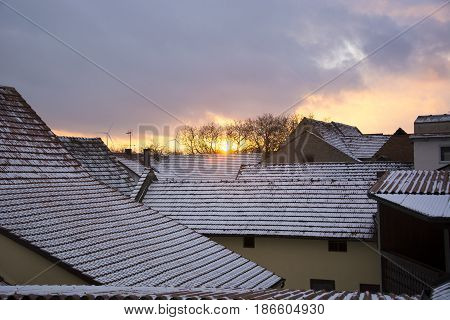 Sunset over snow covered rooftops in January in Bavaria, Germany