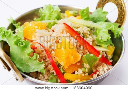 Indian restaurant dish, quinoa salad in copper bowl isolated on white. Lettuce and fruits mix. Eastern local cuisine food.