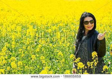 Beauty smiling woman giving thumb up in rape field