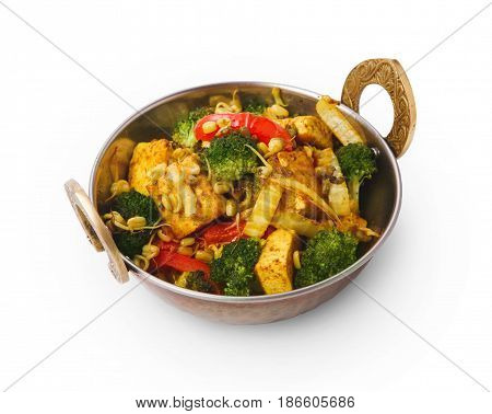 Restaurant vegan dish, tofu stir fry in copper bowl isolated on white. Vegetable mix. Eastern indian local cuisine food.