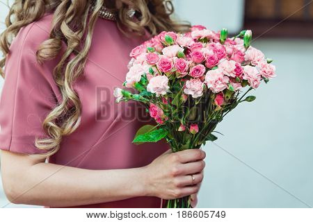 woman in a biege dress holding wedding bouquets of biege carnations and pink roses